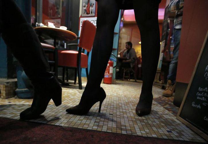 Al parecer los zapatos con tacón hacen lucir más a las damas ante los hombres. En la foto, una mujer luce tacones en un restaurante parisino. (Foto: AP)