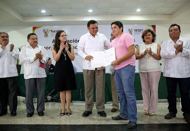 Rolando Zapata Bello entregó los documentos que avalan la plaza magisterial a un grupo de docentes. (Milenio Novedades)
