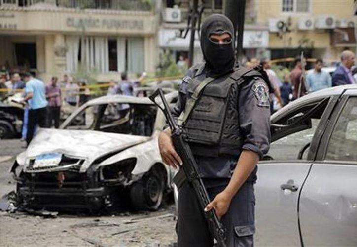 Un policía egipcio vigila el sitio donde se registró un atentado contra el convoy en el que viajaba el fiscal estatal de Egipto An en el distrito de Heliópolis, El Cairo, este lunes. (Foto AP/Amr Nabil)