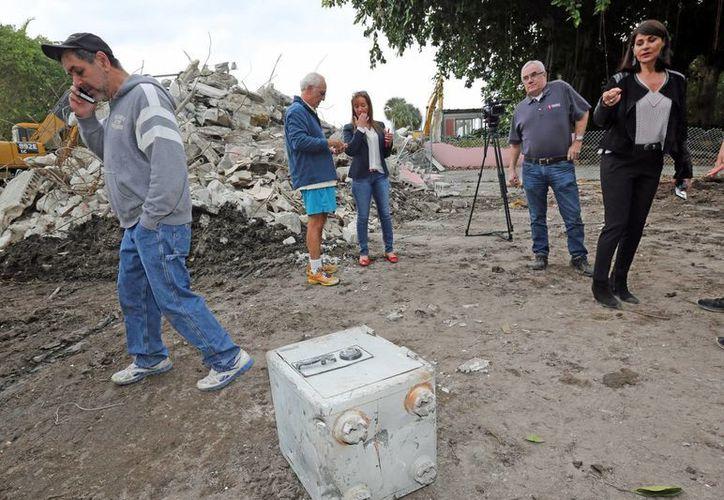 Christian de Berdouare, centro, y su esposa Jennifer Valoppi, derecha, mientras decidían en dónde almacenar la primera caja fuerte que encontraron en la antigua mansión perteneciente a Pablo Escobar en Miami Beach. (C. M. Guerrero / El Nuevo Herald vía AP)