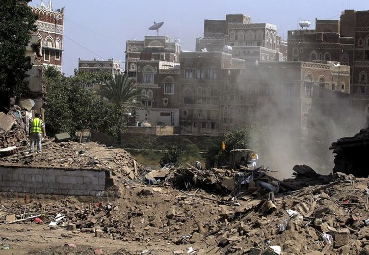 Coalición árabe ataca a convoy de autos y autobuses que huyen de la guerra civil. Imagen de varios yemenís que observan los escombros de unos edificios históricos presuntamente derribados por un bombardeo en Saná, Yemen. (Archivo/EFE)