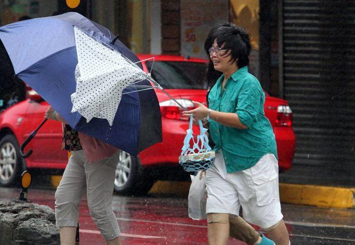 Ante los efectos del tifón Fitow, mujeres llevan sus sombrillas, una de éstas vencida por el viento, en Taipei, Taiwán. (Agencias)