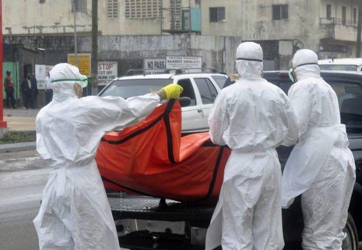 Trabajadores de la salud trasladan el cadaver de un enfermo de ébola en Liberia. (Agencias)