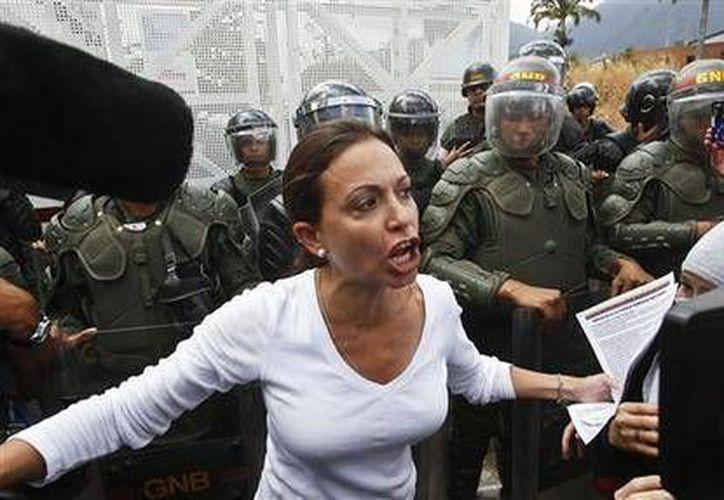 Congresista opositora venezolana María Corina Machado habla a la prensa frente a una hilera de guardias bolivarianos en Caracas, Venezuela el pasado 16 de marzo. (Agencias)