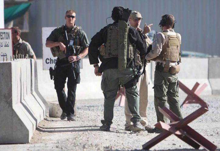 Oficiales de seguridad extranjeros inspeccionan tras un ataque suicida cometido hoy contra el Departamento de Narcóticos afgano en Kabul. (EFE)