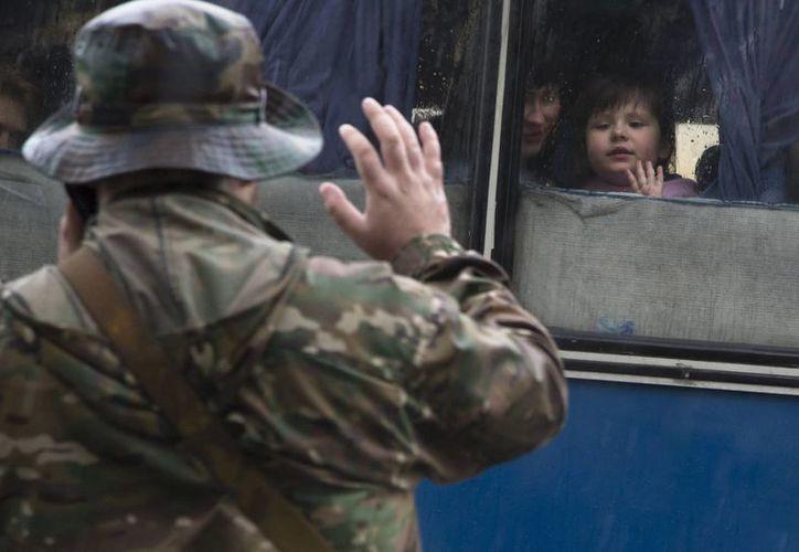 Un combatiente en Donetsk, Ucrania, se despide de su familia, como ocurre con muchas que se van para hallar refugio más allá de la zona del conflicto. (Foto: AP)