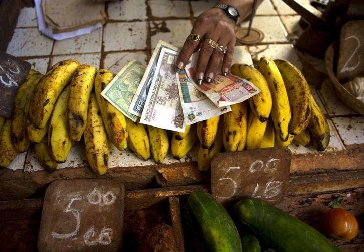 Una vendedora de alimentos muestra pesos convertibles,conocidos como CUC (los dos de la derecha) junto a pesos tradicionales en un mercado de La Habana. (Agencias)
