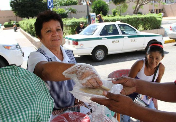 Las mujeres se caracterizan por vender en las calles frutas peladas, alimentos fritos y postres. (Tomás Álvarez/SIPSE)