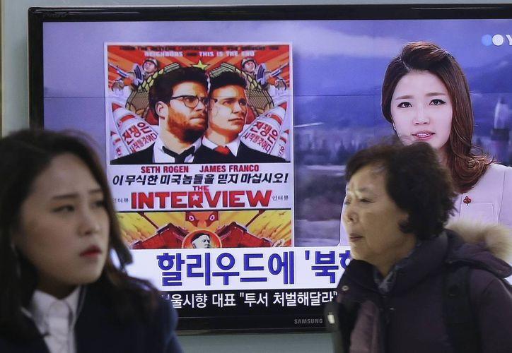 """Gente pasa de largo mientras en una pantalla se anuncia la cinta """"The Interview"""" en Corea del Sur, de donde es el activista que pretende lanzar por globos los dvd con el filme sobre el complot contra el líder norcoreano Kim Jung Un. (Foto: AP)"""