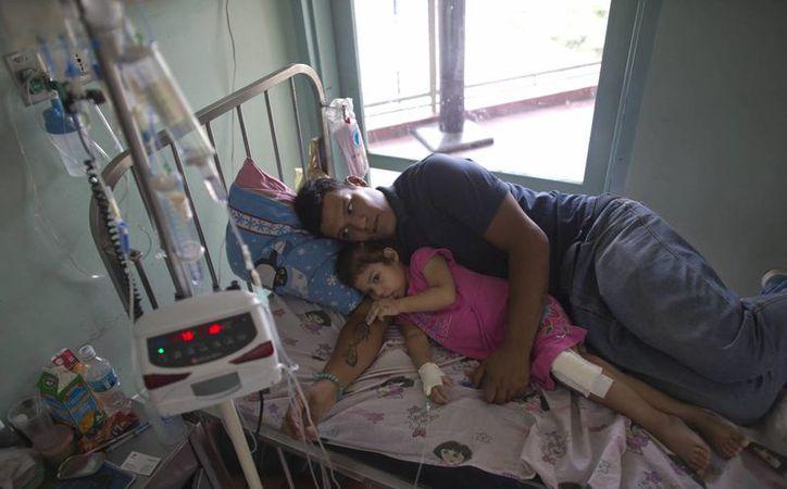 Maykol Pacheco se acurruca con su hija Ashley en su cama de hospital, durante su estancia de dos meses en el Hospital Universitario de Caracas, en Venezuela. (AP/Ariana Cubillos)