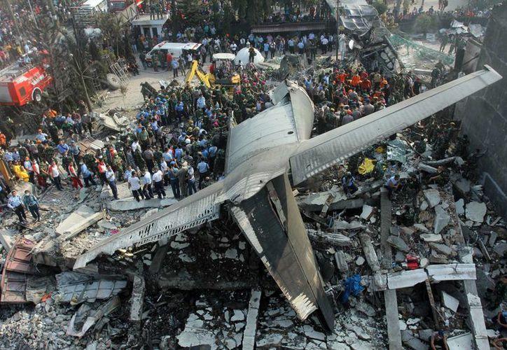 Rescatistas buscan víctimas en el lugar donde se estrelló un avión militar de transporte, en Medan, en el norte de la isla de Sumatra, Indonesia, hoy el martes. (Foto AP/Yudha Lesmana)