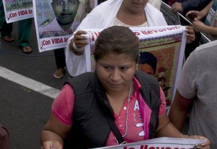 Familiares de los normalistas de Ayotzinapa marchan en el Zócalo de la Ciudad de México sosteniendo imágenes de los jóvenes desaparecidos. (Agencias)