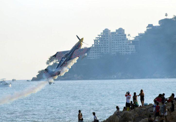 No solo se planea una gran inversión para combatir la inseguridad en Guerrero, sino que ya se realizan eventos masivos para reactivar su economía, como en esta foto en la que aparece un piloto durante una acrobacia aérea en Acapulco. (Notimex)