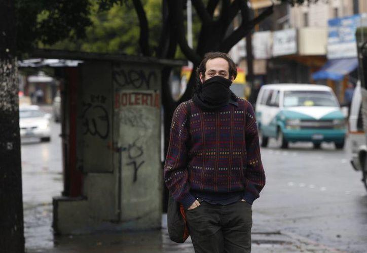 En el centro del país habrá cielo medio nublado con un ambiente templado. Posibilidad de lloviznas en el Estado de México, Ciudad de México, Hidalgo y Puebla. Imagen de contexto de un hombre abrigado por el frío al momento de cruzar una calle. (Notimex)