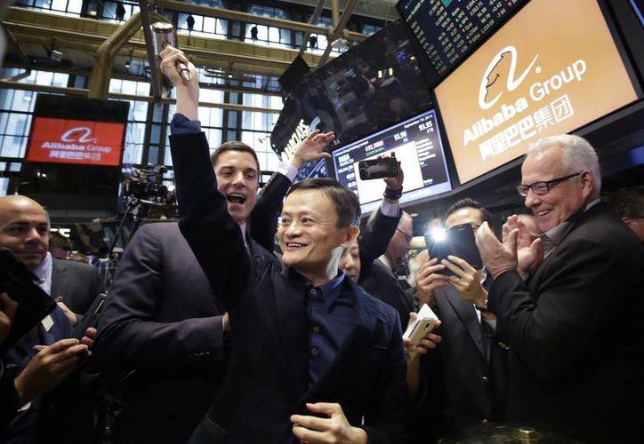 Jack Ma (c), fundador de Alibaba, plantea una maza ceremonial antes de golpear una campana durante la salida a bolsa de su compañía en la Bolsa de Valores de Nueva York. (Agencias)