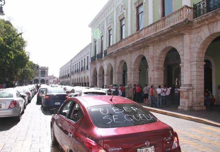 Este jueves 23 de junio entra en vigor la ley que regula los servicios de taxis contratados vía app. La imagen corresponde a una protesta de choferes de Uber, en Mérida, y está utilizada solo como ilustración. (Archivo/SIPSE)