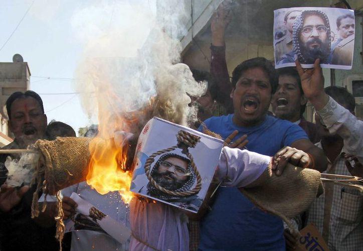 Algunas personas celebraron la ejecución de Guru quemando impresiones con su rostro. (AP)