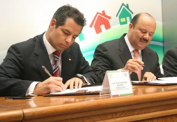 El gobernador de Chihuahua, César Duarte (d) y el director Nacional del INFONAVIT, Alejandro Murat Hinojosa. (Notimex)