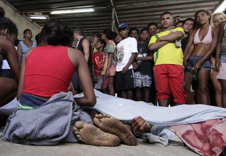 Vecinos y familiares de un hombre abatido en la Ciudad de Dios, en Río de Janeiro, Brasil, el domingo 20 de noviembre de 2016. Los operativos policiales en las favelas se tornan cada vez más violentos. (AP/Fabio Teixeira)