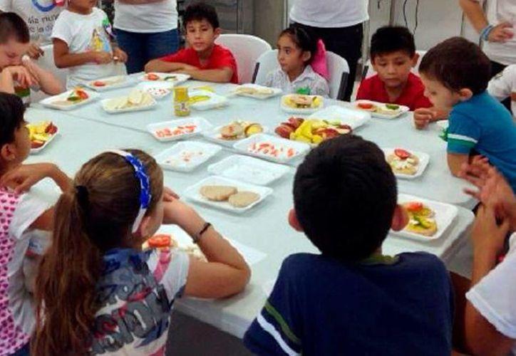 Los padres están fallando en la forma de alimentar a los hijos, esto debido a la desidia de prepararles algo sano. Imagen de un grupo de niños en un comedor. (Milenio Novedades)