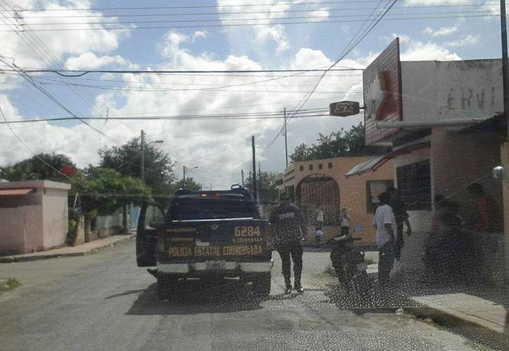 Elementos de la SSP recaban datos acerca del hombre encontrado muerto en una banqueta de la colonia Salvador Alvarado Oriente. (Luis Fuente/SIPSE)