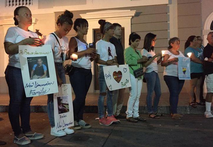 Gente con carteles y velas se reúnen en Ponce, Puerto Rico, durante una vigilia por las víctimas de la masacre en el antro gay Pulse en Orlando, Florida. (Agencias)
