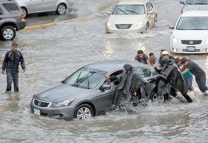 Policías municipales y automovilistas retiran un vehículo varado por las inundaciones en Monterrey. (Milenio)