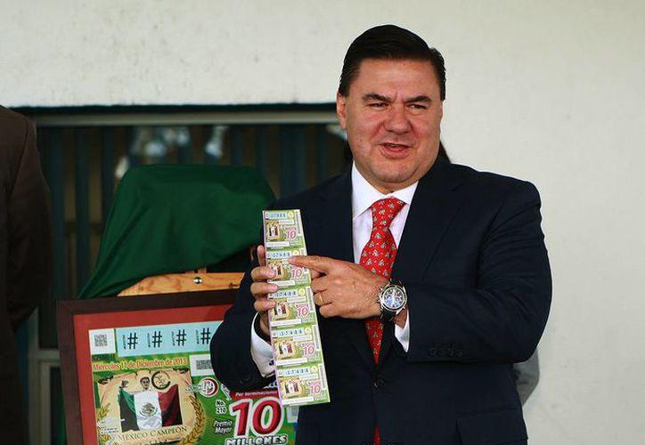 El director general de la Conade, Jesús Mena Campos muestra el billete conmemorativo del 25 Aniversario del organismo. (Foto Conade)