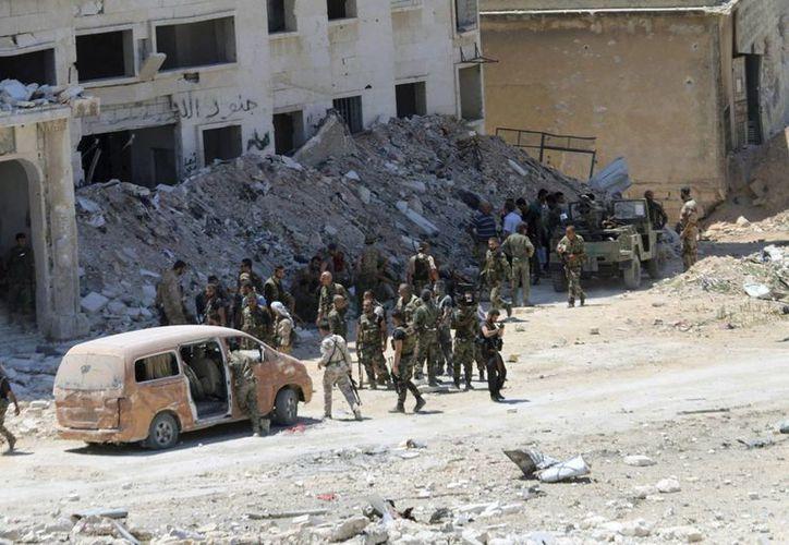 Fotografía facilitada por la Agencia de Noticias Árabe Siria (SANA), que muestra a soldados gubernamentales mientras patrullan por los barrios de Al Layramoun y Bani Zein tras arrebatárselas a los rebeldes en la provincia de Alepo, el pasado mes de julio. (Archivo/EFE)