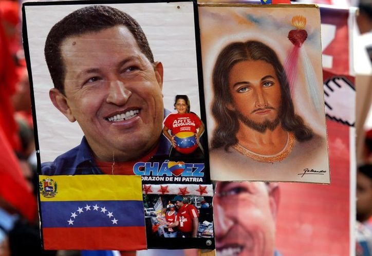 Una mujer en una marcha chavista sostiene el un retrato de Chávez al lado de una imagen de Jesús. (Agencias)