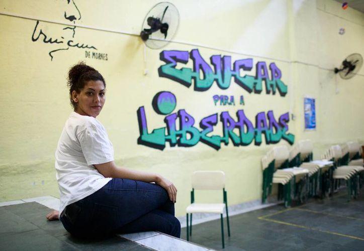 """La interna transexual Estefanie Ferraz posa para una fotografía junto a un mural que dice """"Educar para la libertad"""" en la prisión Evaristo de Moraes donde cumple sentencia, en Río de Janeiro, Brasil. (AP Foto/Mauro Pimentel)"""
