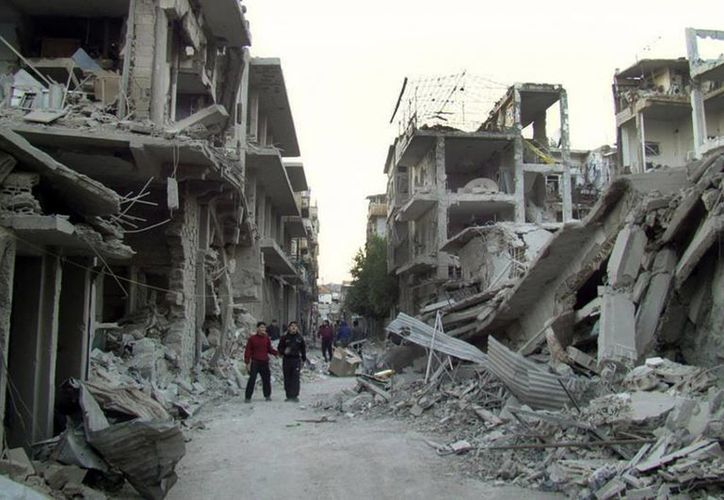 Ciudadanos sirios caminan en una calle destruida por aviones de guerra de las fuerzas sirias en 2012. (Agencias)