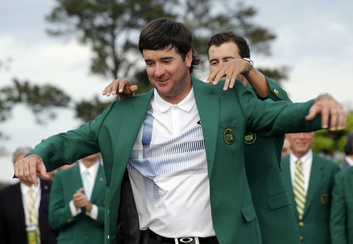 Bubba Watson se acomoda la chaqueta verde como campeón del Masters de Augusta, con la ayuda del monarca vigente Adam Scott. (AP)