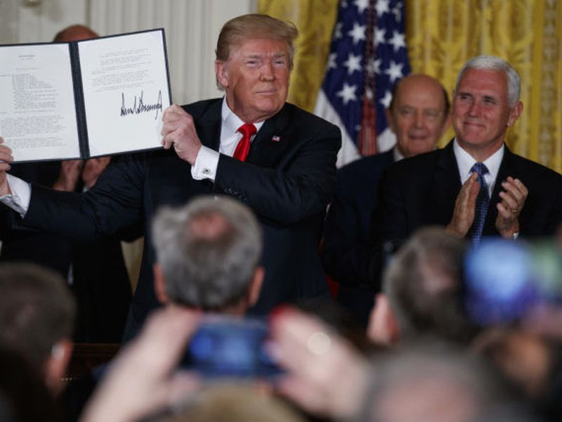 "President Donald Trump shows off a ""Space Policy Directive"" after signing it during a meeting of the National Space Council in the East Room of the White House."