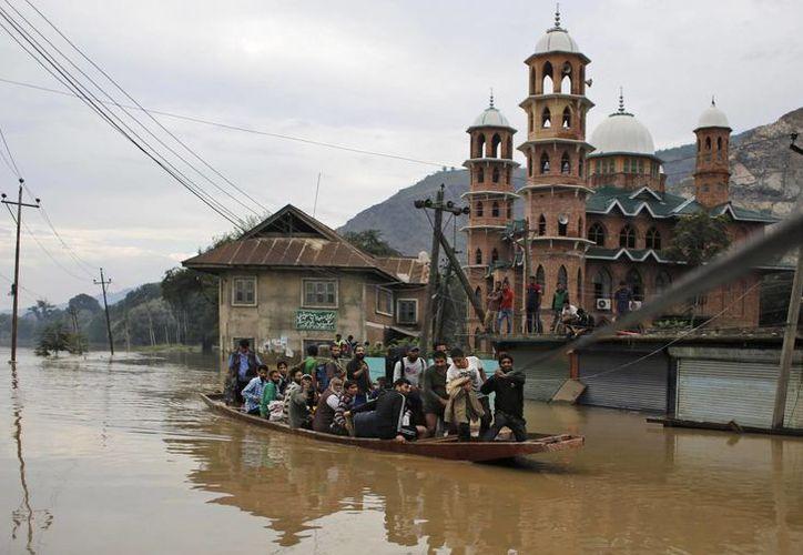 Los voluntarios locales sacan a víctimas de la inundación en Srinagar, India. (Agencias)