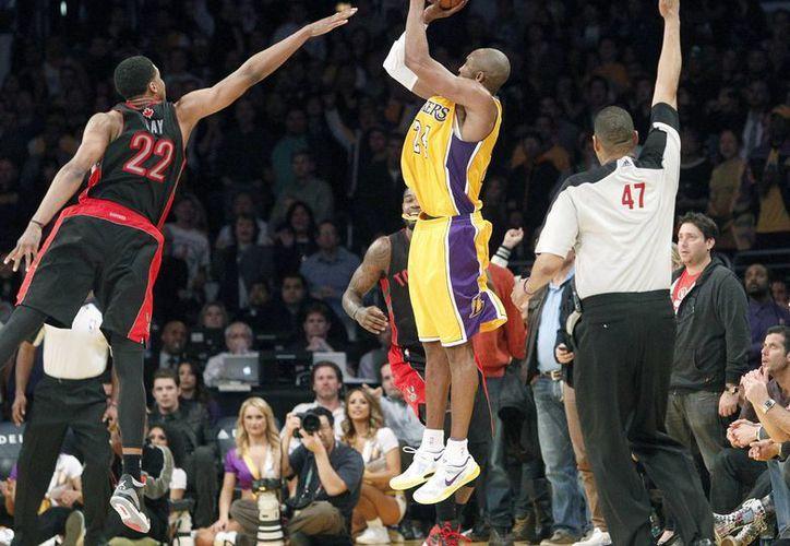 Kobe Bryant (24), de los Lakers de Los Angeles, realiza un tiro de tres puntos para empatar el juego a los Raptors de Toronto en el tiempo regular, frente a Rudy Gay (22). (Agencias)