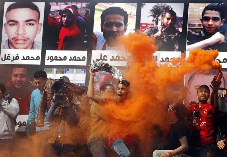Un seguidor del club de futbol  Al-Ahly club grita junto a un cartel con las fotos de las víctimas de la tragedia en Port Said. (Agencias)
