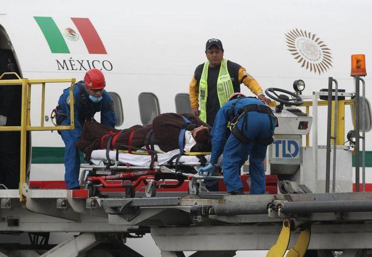 Paramedicos mexicanos descienden del avión presidencial el 18 de septiembre de 2015, con uno de los turistas mexicanos que resultaron heridos en un ataque mientras recorrían Egipto, en Ciudad de México, México. (EFE/Archivo)