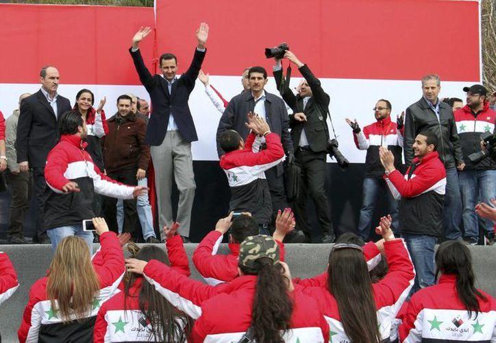 El presidente sirio Bashar al Asad, saluda tras pronunciar un discurso ante miles de sus seguidores. (EFE/Archivo)