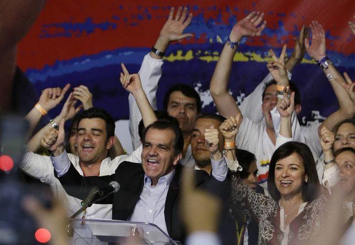 El opositor Oscar Iván Zuluaga celebra con sus seguidores su triunfo en las elecciones del domingo en Colombia, con el cual ha forzado a una segunda vuelta electoral con el presidente Juan Manuel Santos. (AP)