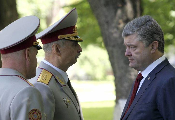 El presidente ucraniano Petro Poroshenko, derecha, se reúne con el ministro de Defensa interino Mijailo Koval, centro, en Kiev, Ucraania. (Agencias)
