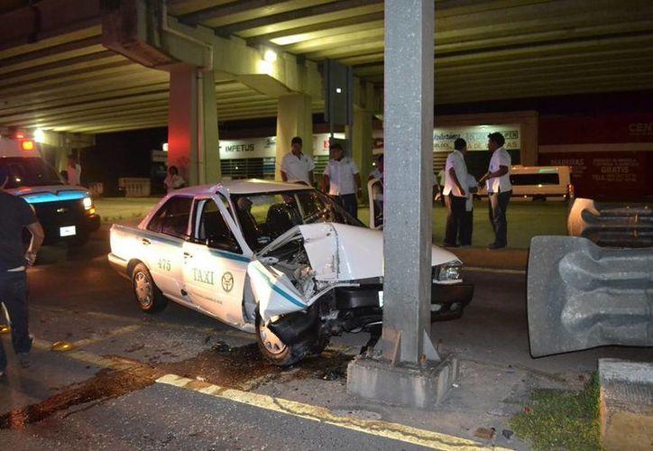 El taxista estampó su unidad contra un poste de luz tras quedarse dormido al volante, luego abandonó su vehículo y a su pasajera.  (Redacción/SIPSE)