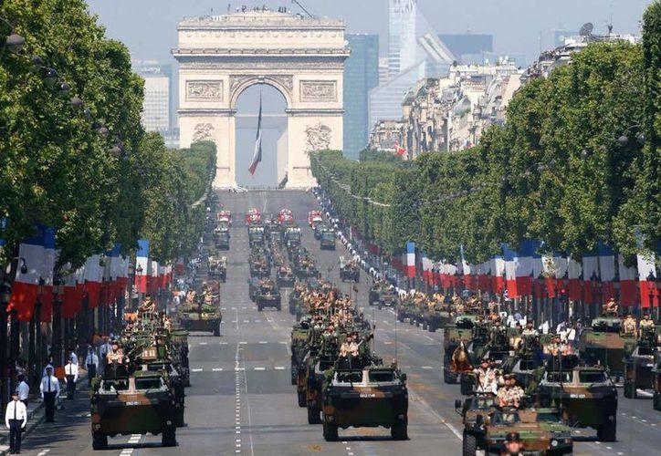 Vehículos de combate desfilan en París, teniendo como fondo el Arco del Triunfo, en la celebración del Día Nacional. (Agencias)