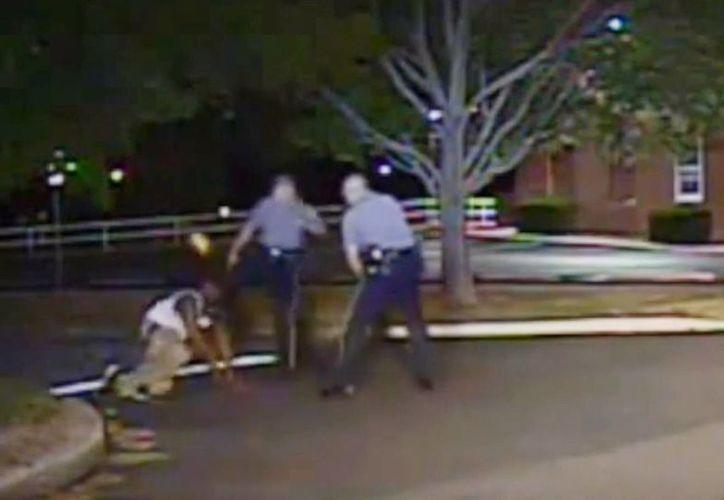 En esta imagen de 2013, tomada de una cámara policial, y difundida por la policía de Dover, el oficial Thomas Webster, centro, patea en la cara a Lateef Dickerson mientras este pone las manos sobre el piso. (AP)