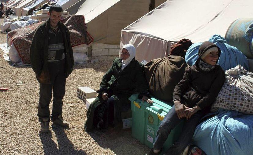 Varios refugiados sirios que abandonaron las localidades de Flita y Yabroud debido a la violencia esperan recibir una tienda de campaña en el campo de refugiados de Arsal, Líbano. (Archivo/EFE)