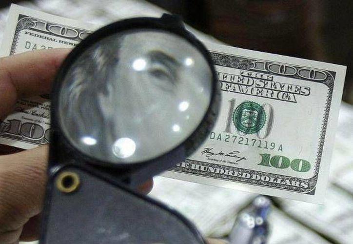 Se requiere de 'ritualizar' el billete de dólar para que este pueda dar suerte. (Jorge Moreno/Milenio Novedades)