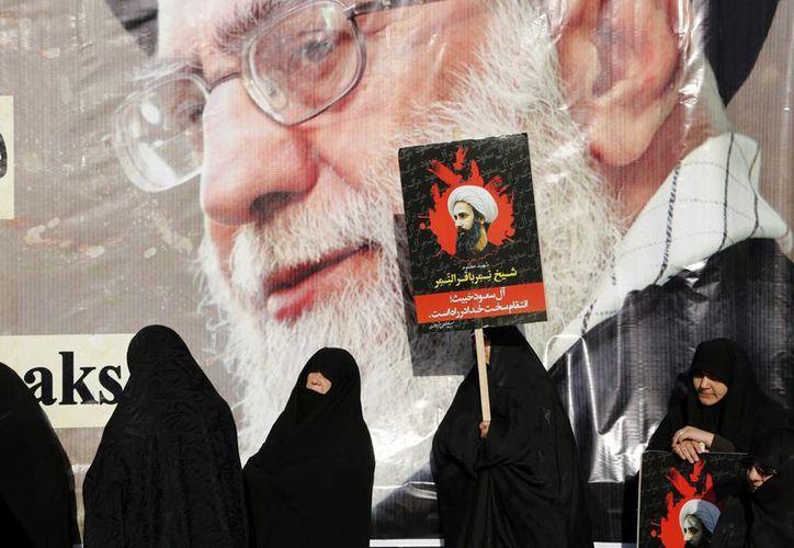 Una mujer iraní muestra un cartel del clérigo y dirigente chií, Nimr Baqir al Nimr, delante de un cartel gigante del líder supremo iraní, ayatolá Ali Jamenei, durante una protesta convocada ayer en Teherán, Irán. (EFE)