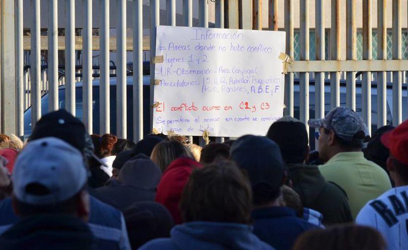 Familiares de los internos leen un cartel colocado en la reja del penal de Topo Chico, tras el motín que se registró hace unos días. (Agencias)