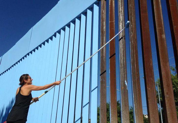La artista Ana Teresa Fernández pinta la valla fronteriza de color azul para 'bajar el cielo' como parte del plan 'Borrando la Frontera'. (Agencias)