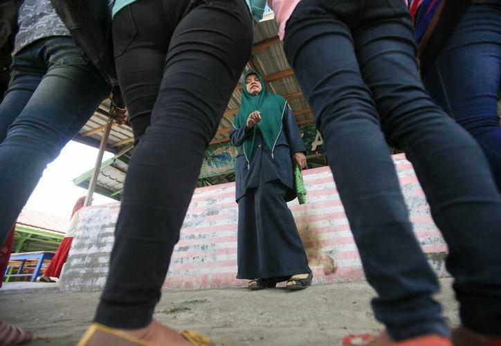 Una mujer policía reprende a un grupo de mujeres detenidas por vestir con vaqueros estrechos durante una redada policial en Banda Aceh, Indonesia. (Archivo/EFE)